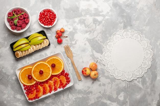 Vista de cima em fatias de laranjas com framboesas em uma mesa clara