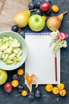 Vista de cima em fatias de maçã verde junto com diferentes frutas frescas e um bloco de notas na mesa azul-escuro biscoito de frutas biscoito doce fresco