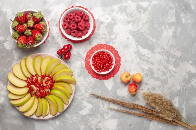 Vista de cima em fatias de maçãs verdes com framboesas e morangos em uma superfície branca fruta baga tropical exótica fresca