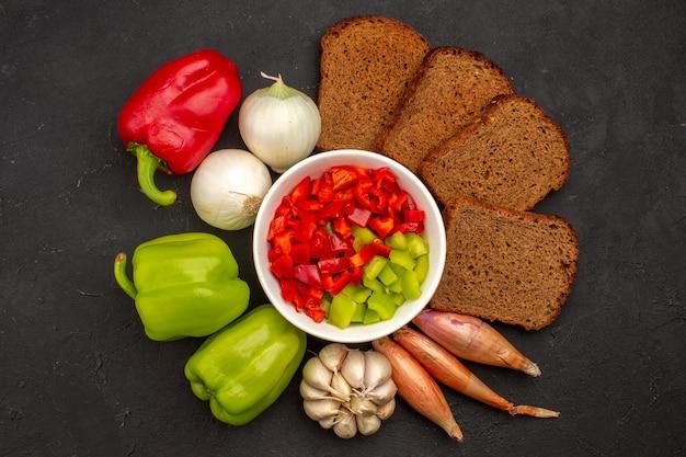 Vista de cima em fatias de pimenta com legumes e pão preto no espaço escuro