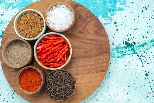 Vista de cima em fatias de pimenta vermelha com pimenta e temperos diferentes na foto colorida de produto de sal de pimenta de fundo azul claro