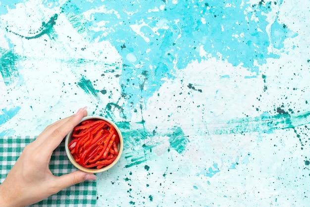 Vista de cima em fatias de pimenta vermelha dentro do pequeno prato sobre o ingrediente alimentar da foto colorida de fundo azul claro