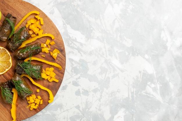 Vista de cima em fatias de pimentão com dolma de folhas na mesa branca