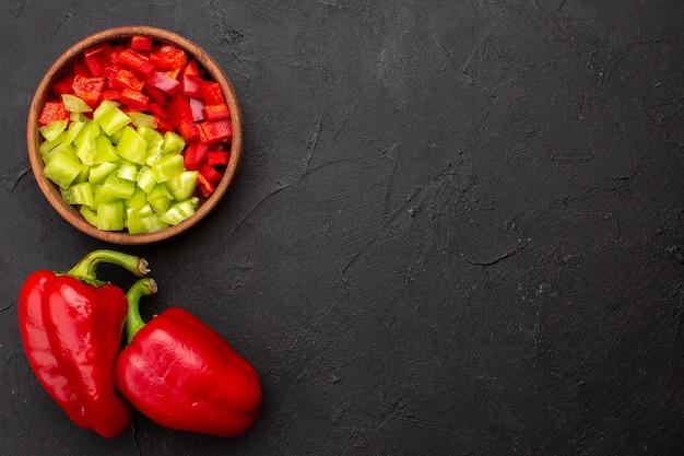 Vista de cima em fatias de pimentão com pimentão vermelho em uma refeição quente picante de fundo cinza