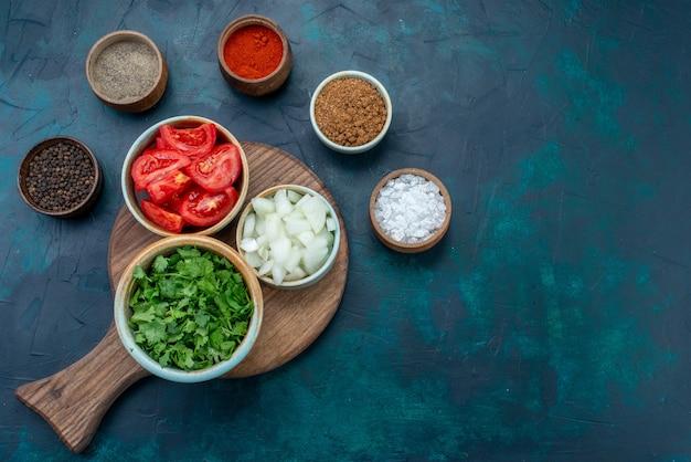 Vista de cima em fatias de vegetais frescos, tomates e cebolas com verduras e temperos na mesa azul-escura comida jantar refeição vegetais