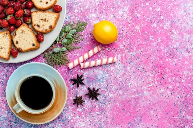 Vista de cima em fatias deliciosas de bolos com morangos vermelhos frescos e uma xícara de café na mesa rosa claro