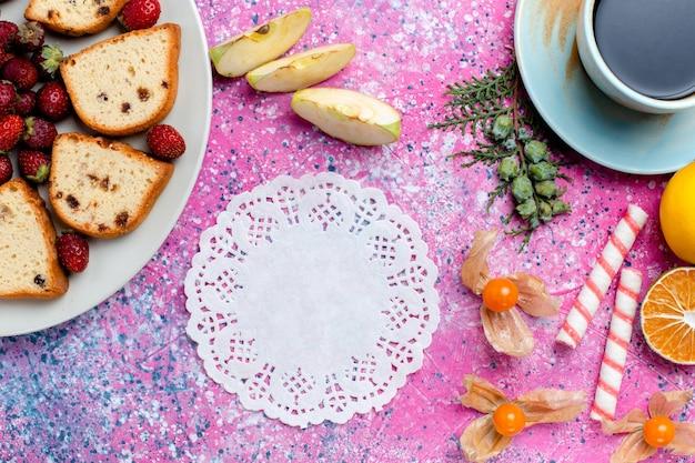 Vista de cima em fatias deliciosas de bolos com uma xícara de café e morangos vermelhos na mesa rosa claro