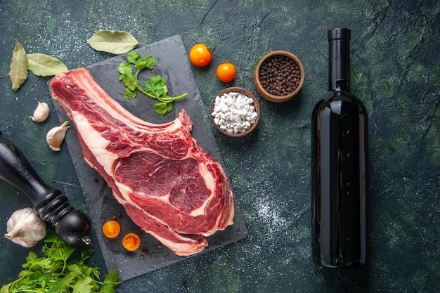 Vista de cima em uma fatia grande de carne crua com pimenta e verduras na superfície escura