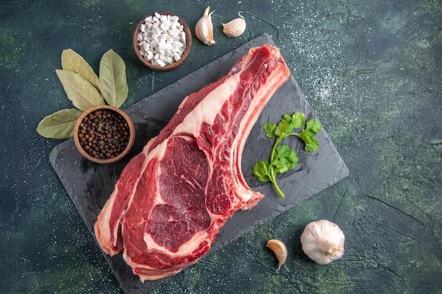 Vista de cima em uma grande fatia de carne crua com pimenta na superfície escura