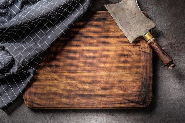 Vista de cima em uma tábua de corte vazia, com cutelo vintage e toalha de chá xadrez escura em cima com um fundo escuro