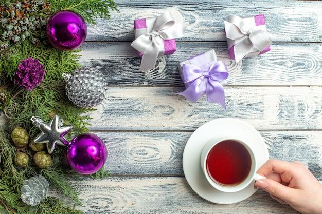 Vista de cima enfeites de natal, uma xícara de chá feminina, pequenos presentes, ramos de árvore do abeto, brinquedos de natal na superfície de madeira