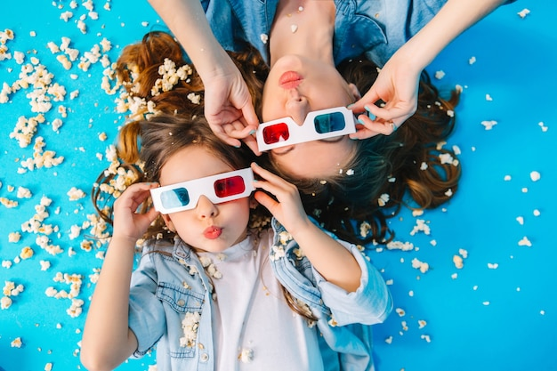 Vista de cima engraçada mãe e filha deitada no chão, se divertindo para a câmera na pipoca isolada sobre fundo azul. família elegante em roupas jeans, usando óculos 3d e expressando felicidade