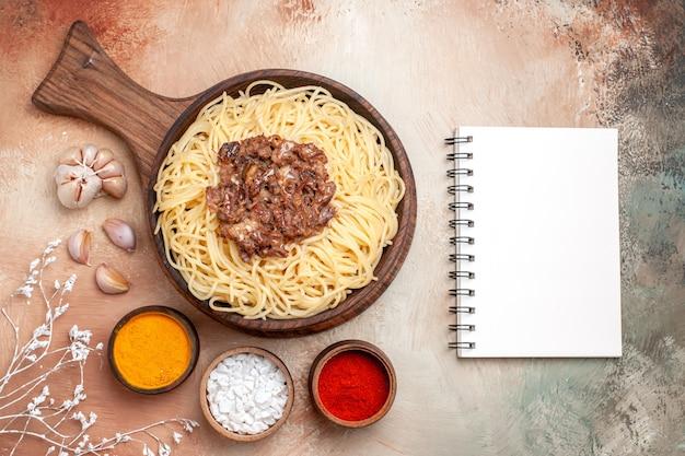 Vista de cima espaguete cozido com carne moída em piso de madeira, tempero de prato de massa