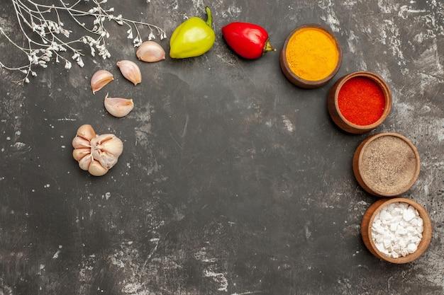 Vista de cima especiarias na mesa especiarias coloridas em uma tigela pimenta bola de alho na mesa escura