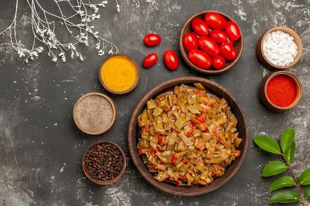 Vista de cima especiarias na mesa taças de especiarias coloridas, pimenta preta e tomate ao lado do prato de feijão verde na mesa preta