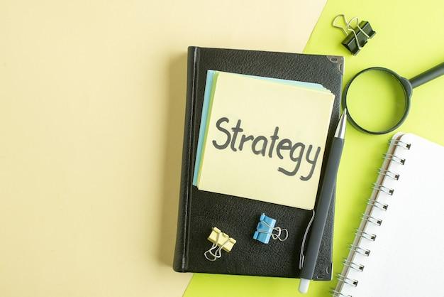 Vista de cima estratégia nota escrita com bloco de notas preto e caneta sobre fundo verde caderno trabalho salário faculdade cor escola negócios