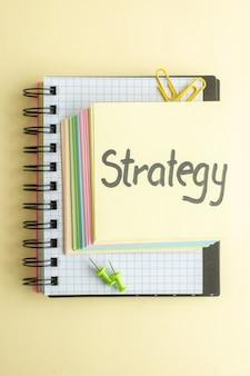 Vista de cima estratégia nota escrita com notas de papel coloridas sobre fundo claro bloco de notas trabalho de negócios caneta escritório dinheiro banco cor caderno de trabalho