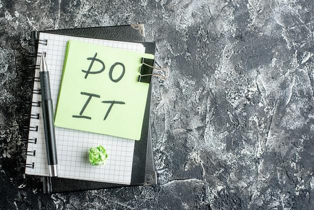Vista de cima faça anotações com caneta de adesivos e bloco de notas em fundo escuro