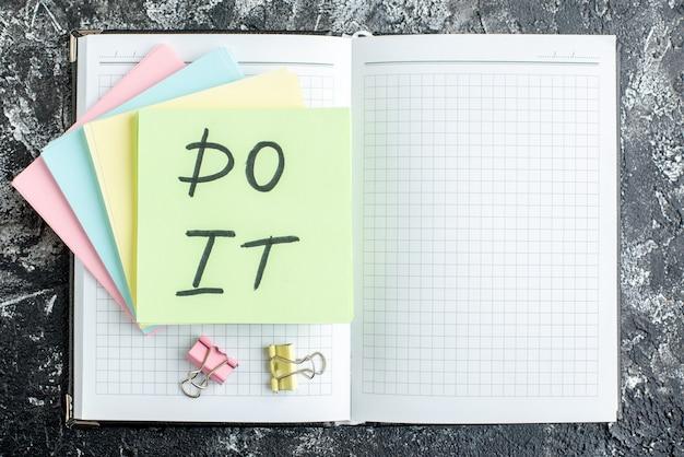 Vista de cima faça nota com adesivos e bloco de notas em fundo cinza escuro