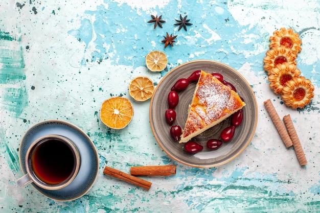 Vista de cima fatia de bolo com biscoitos e xícara de chá na superfície azul bolo de frutas assar torta de biscoito doce