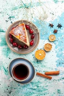 Vista de cima fatia de bolo com dogwoods vermelhos frescos e xícara de chá em uma superfície azul bolo de frutas assar torta biscoito doce