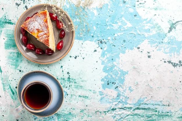 Vista de cima fatia de bolo com dogwoods vermelhos frescos e xícara de chá no fundo azul bolo de frutas assar torta biscoito doce
