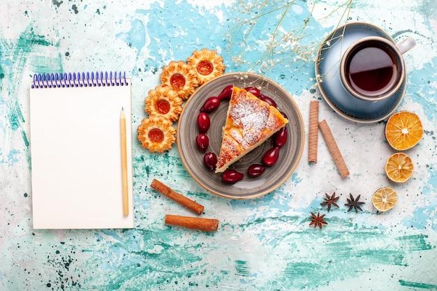 Vista de cima fatia de bolo delicioso com xícara de chá no bolo de mesa azul assar torta de biscoito doce