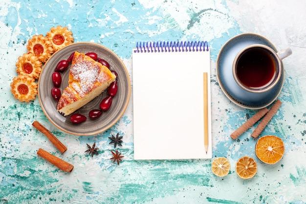 Vista de cima fatia de bolo delicioso com xícara de chá no bolo de superfície azul claro assar torta de biscoito doce