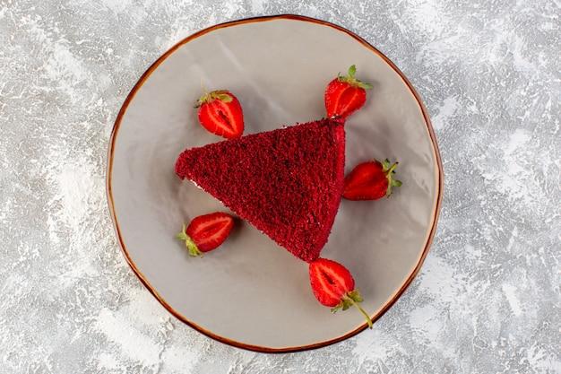 Vista de cima fatia de bolo vermelho pedaço de bolo de frutas dentro do prato com morangos frescos no fundo cinza bolo doce biscoito