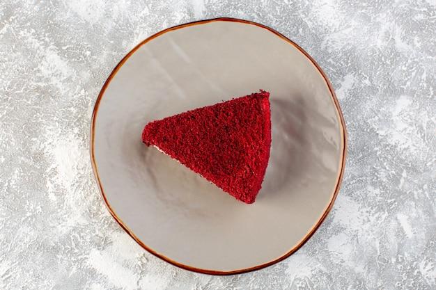 Vista de cima fatia de bolo vermelho pedaço de bolo de frutas dentro do prato no fundo cinza bolo doce chá