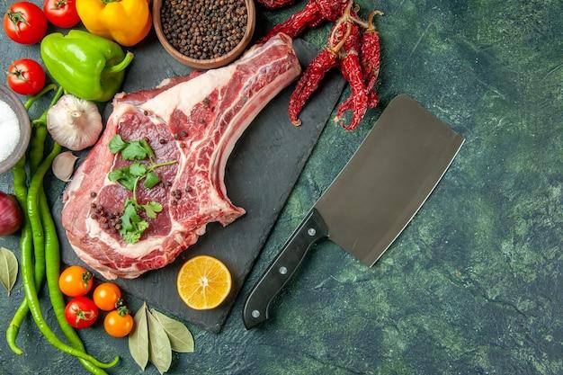 Vista de cima fatia de carne crua com vegetais frescos e pimenta no fundo azul escuro alimentos carne cozinha animal frango vaca açougueiro