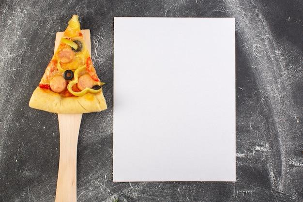 Vista de cima fatia de pizza com azeitonas pretas, tomates e salsichas na colher de pau, perto de um papel vazio na mesa cinza.