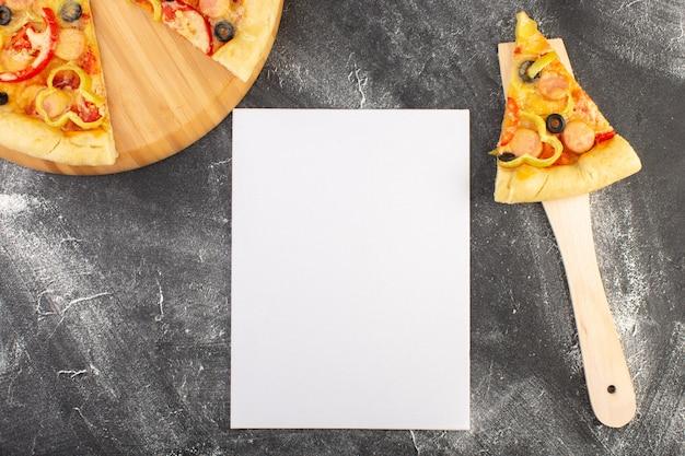 Vista de cima fatia de pizza com azeitonas pretas, tomates e salsichas na colher de pau perto do papel vazio na mesa cinza comida massa italiana pizza refeição