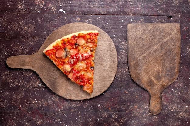 Vista de cima, fatia de pizza gostosa com salsichas, queijo, tomates e azeitonas no fundo de madeira marrom.