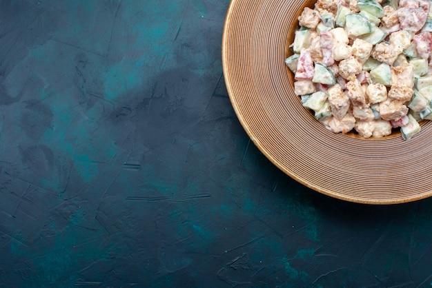 Vista de cima, fatia saborosa de salada de vegetais com maionese dentro do prato na refeição de salada de vegetais de fundo azul escuro