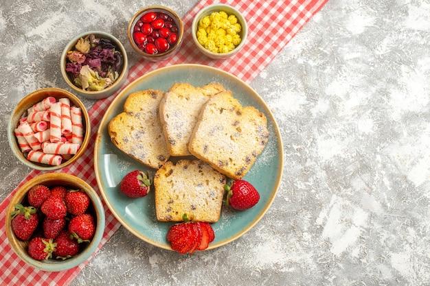 Vista de cima fatias de bolo com morangos frescos e doces em torta de frutas doces