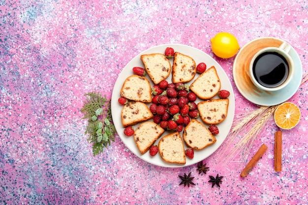 Vista de cima fatias de bolo com morangos frescos e xícara de café no bolo de mesa rosa assar biscoitos doces torta de cor