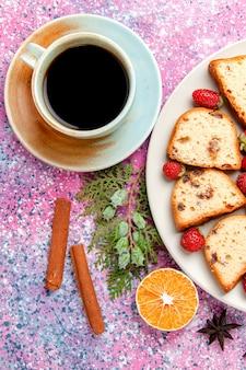 Vista de cima fatias de bolo com morangos vermelhos frescos e xícara de café na superfície rosa