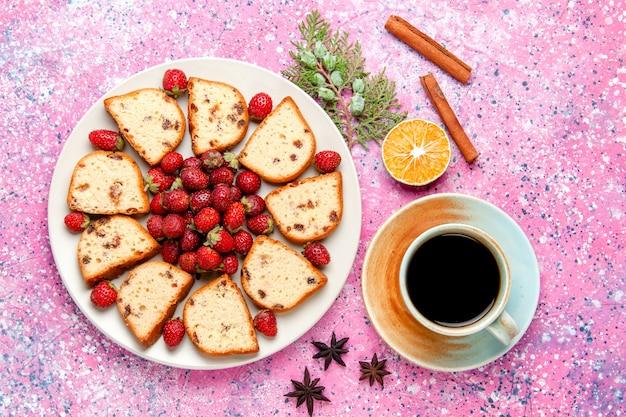 Vista de cima fatias de bolo com passas dentro do prato com morangos frescos em um bolo de mesa rosa claro asse biscoito doce torta de biscoito de açúcar