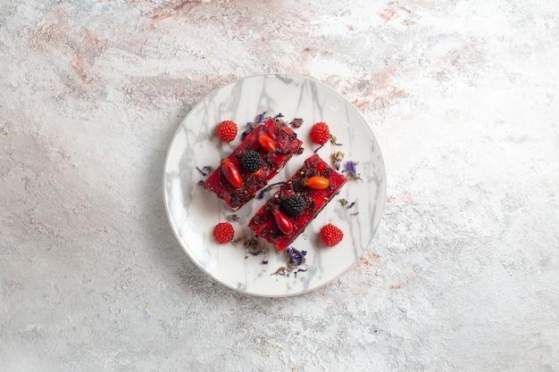 Vista de cima fatias de bolo de frutas saborosas com creme vermelho sobre fundo branco