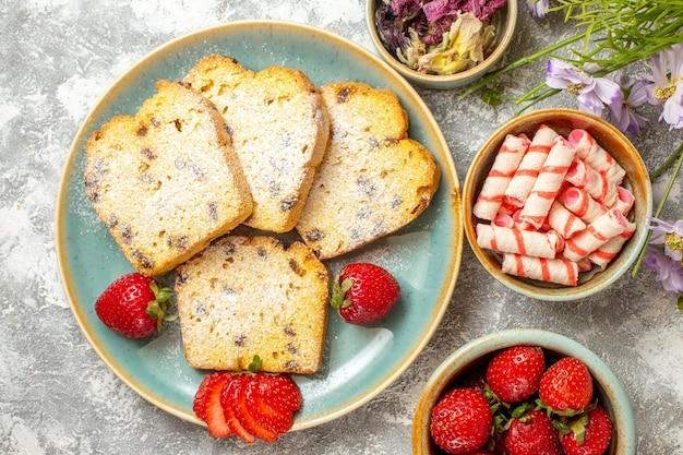 Vista de cima fatias de bolo saborosas com morangos na luz