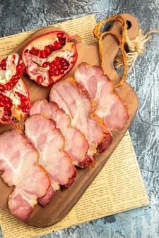 Vista de cima fatias de carne cortadas romã em uma tábua na superfície cinza do jornal