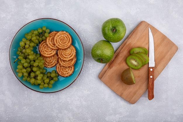 Vista de cima fatias de kiwi com uma faca em uma tábua de cortar com maçãs verdes e uvas verdes com biscoitos em um prato em um fundo branco