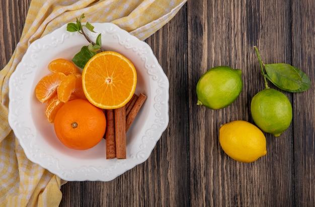 Vista de cima fatias de laranja descascadas com canela em um prato e limão com limas em fundo de madeira