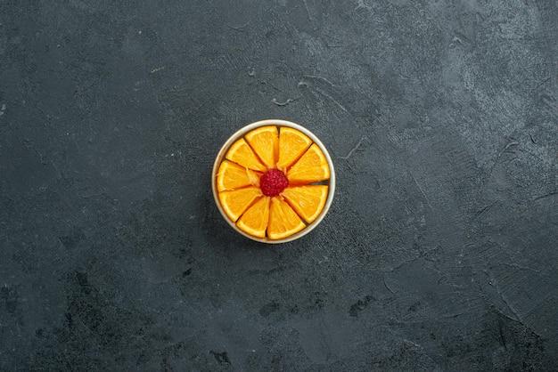 Vista de cima fatias de laranja frescas dentro de um pequeno prato em uma superfície escura com frutas cítricas frescas