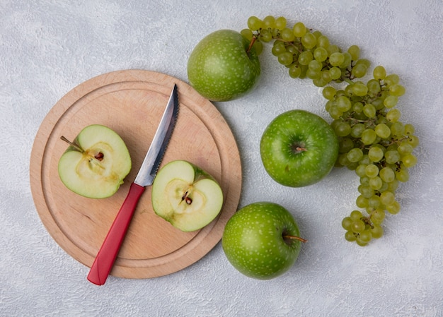 Vista de cima fatias de maçã verde com uma faca em um suporte com uvas verdes em um fundo branco