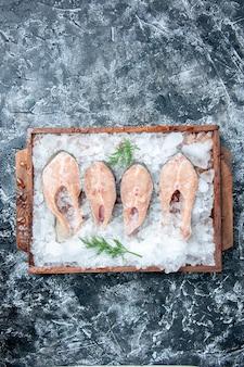 Vista de cima fatias de peixe cru com gelo em uma placa de madeira em um fundo cinza com espaço livre