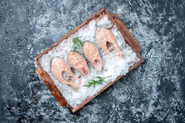 Vista de cima fatias de peixe cru com gelo em uma placa de madeira no local de cópia de fundo cinza