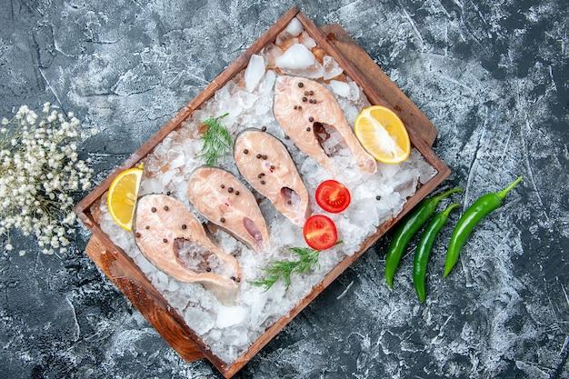 Vista de cima fatias de peixe cru com gelo na tábua de madeira com pimenta verde na mesa