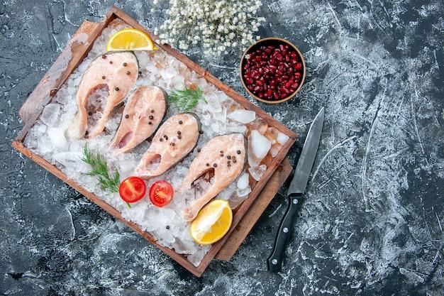 Vista de cima fatias de peixe cru com gelo na tábua de madeira e sementes de romã em uma tigela pequena no lugar da cópia da mesa